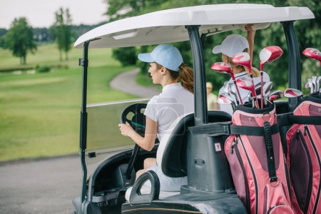back view of female golfers in caps riding golf cart with equipment at golf course