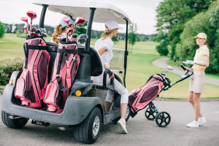 smiling female golf players at golf cart getting ready for game at golf course