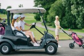 side view of female golfers in caps in golf cart and friend talking on smartphone at golf course