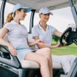Smiling female golfers in caps riding golf cart at...