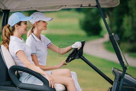 side view of female golfers in caps riding golf cart at golf course