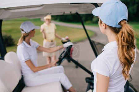 partial view of female golf players in caps at golf course