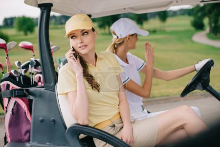 female golfer talking on smartphone while riding in golf cart together with friend at golf course