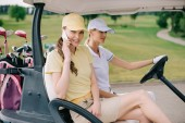 """Постер, картина, фотообои """"Улыбающиеся женщина гольфист, говорить на смартфоне при езде в корзину гольф вместе с другом на гольф-поле"""""""