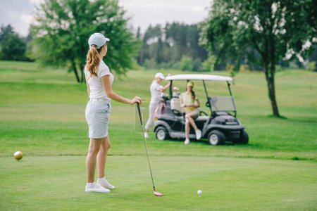 selective focus of woman with golf club looking at friends resting at golf cart on green lawn