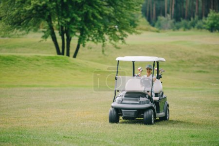 woman in cap riding golf cart at golf course on summer day
