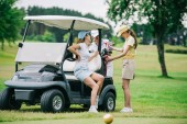 happy women in polos and caps at golf cart getting ready for game