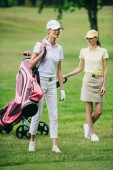 selective focus of women in caps with golf gear on golf course