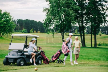 group of female golf players in caps with golf equipment at golf course on summer day