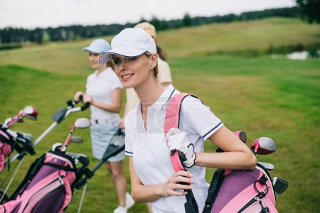 smiling women in caps with golf equipment on golf course