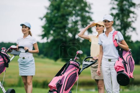 portrait of women in caps with golf equipment on golf course