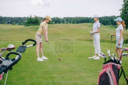side view of woman in cap playing golf while friends standing near by at golf course