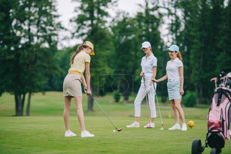 woman in cap playing golf while smiling friends standing near by at golf course
