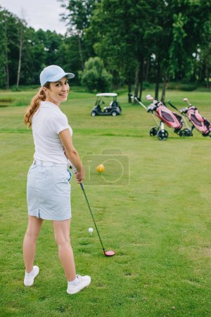 side view of smiling female golf player in cap with golf club standing at golf course