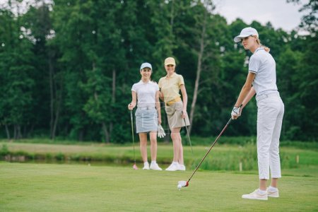 selective focus of woman in cap playing golf while friends standing near by at golf course