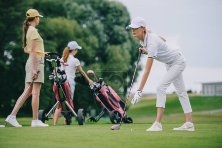 selective focus of focused woman in cap playing golf with friends near by at golf course