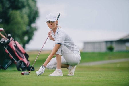 female golf player in cap and golf glove putting ball on green lawn at golf course