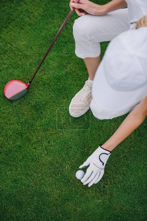 overhead view of woman in cap and golf glove putting ball on green lawn at golf course