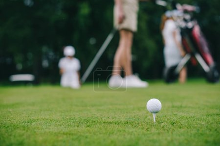 selective focus of golf ball on green lawn and golf players behind