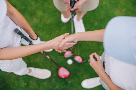overhead view of female golf players with golf clubs shaking hands while standing on green lawn