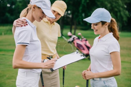 female business partners with notepad discussing project during golf game at golf course