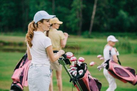 Photo pour Foyer sélectif des femmes en casquettes avec équipement de golf marche sur la pelouse verte au terrain de golf - image libre de droit