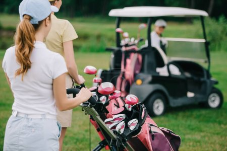 selective focus of female golf players with golf equipment and friend in golf cart behind on green lawn