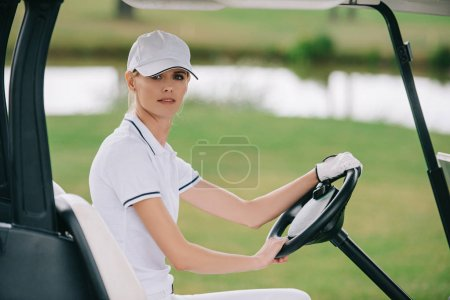 side view of woman in cap and polo riding golf cart at golf course