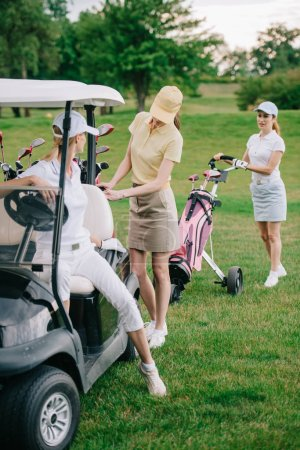 female golf players in caps at golf cart on golf course