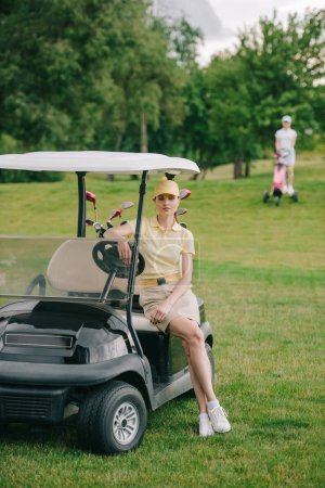 selective focus of female golf player at golf cart on green lawn