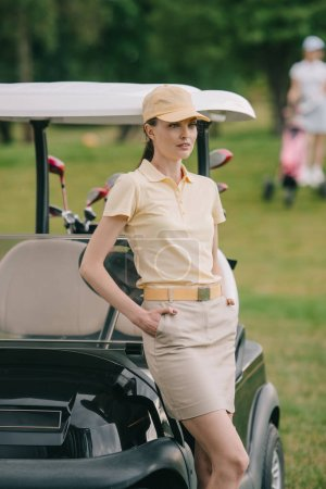 selective focus of female golf player in cap with hands in pockets at golf cart on green lawn