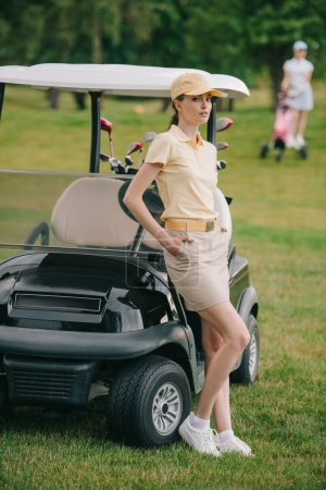 selective focus of female golf player with hands in pockets at golf cart on green lawn