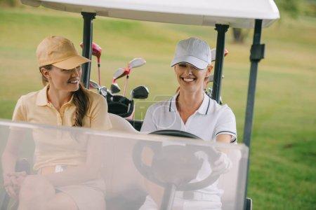 joueurs de golf féminin souriant équitation voiturette de golf au terrain de golf