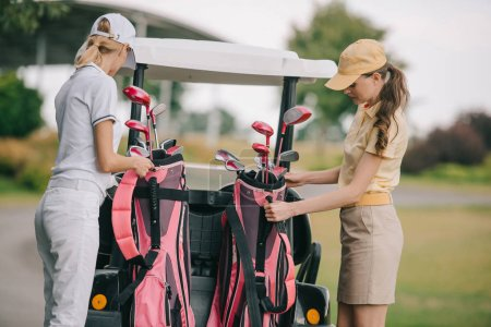 women in polos and caps with golf equipment at golf course on summer day