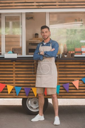 handsome young man in apron smiling at camera while standing with crossed arms near food truck