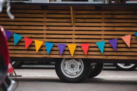 wheels and bottom part of food truck with colorful flags