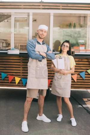young small business owners in aprons standing with crossed arms and smiling at camera near food truck