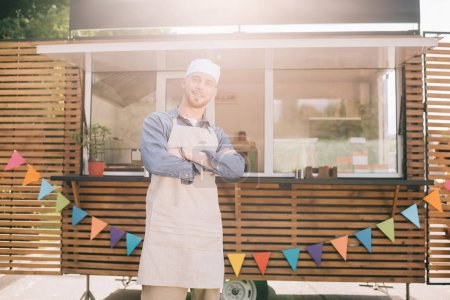 young small business owner standing with crossed arms and smiling at camera near food truck