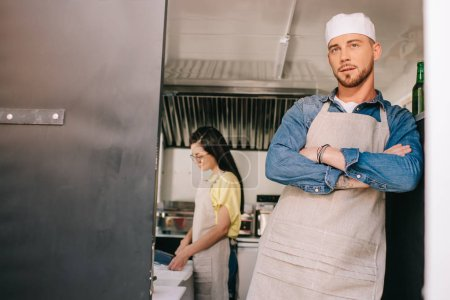 male chef standing with crossed arms while female colleague working behind in food truck