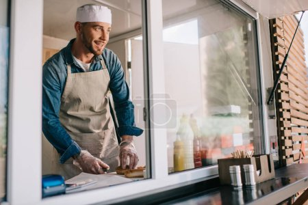 handsome smiling young male chef looking away while cooking in food truck