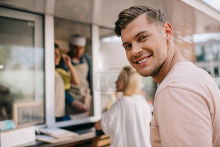 handsome young man smiling at camera while standing in line at food truck