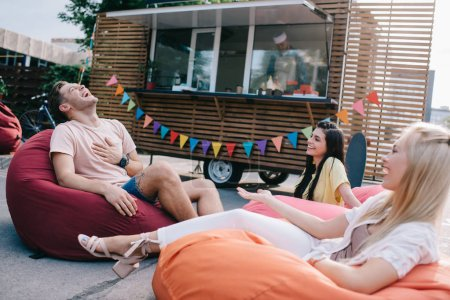 happy young friends laughing while sitting on bean bag chairs near food truck