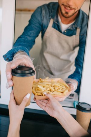 cropped shot of chef giving french fries and coffee to go to client in food truck