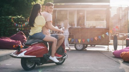 happy couple sitting on motorbike near food truck on street