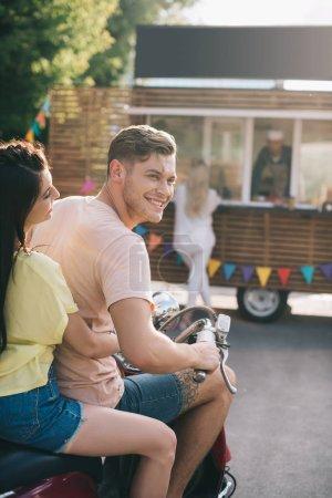 smiling couple sitting on motorbike near food truck on street