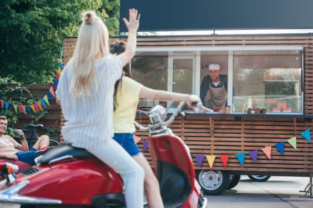 back view of girl on scooter waving hand to chef in food truck