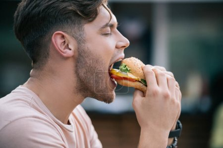 Photo for Side view of man eating tasty burger with closed eyes - Royalty Free Image
