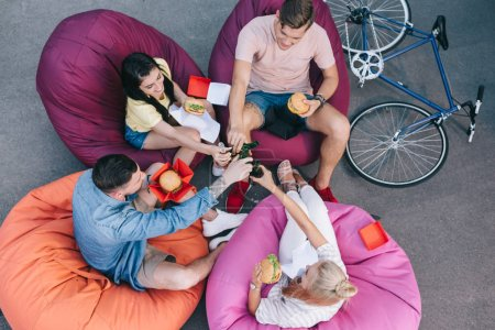 high angle view of friends clinking with bottles of beer and holding burgers on bean bag chairs