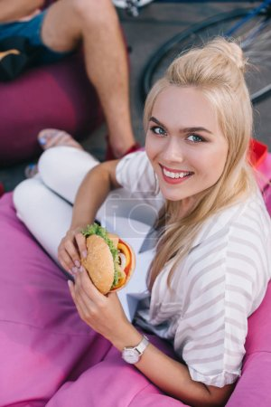 high angle view of attractive woman holding burger and looking at camera