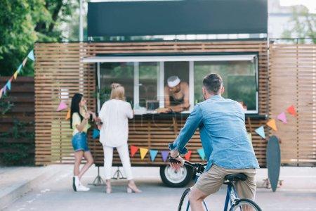 back view of man sitting on bike near food truck